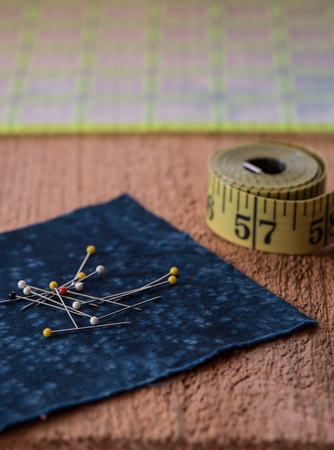 Sewing notions such as fabric, pins, tape measurer and quilting grid sit on top of a rustic wood surface