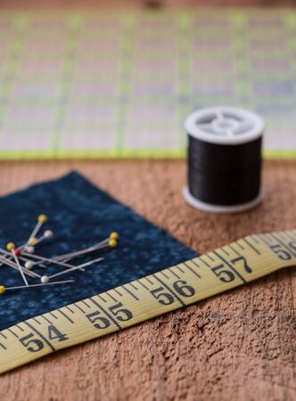 Sewing notions such as fabric, pins, tape measurer, spool of thread and quilting grid sit on top of a rustic wood surface