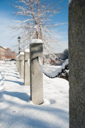 Freshly fallen snow on a granite and chain fence Standard-Bild - 96380899
