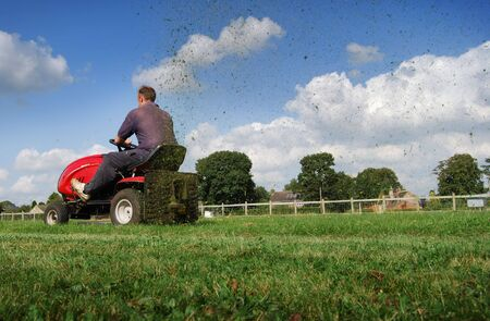 cuttings: Man cutting the lawn with grass cuttings spraying from the back of the mower.