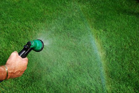 Raindow creating by spray from a hose, focus on the sprayer