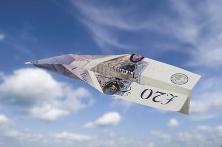 Paper money plane flying through a summer sky