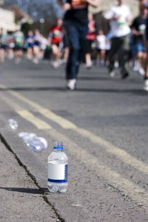 Focus on a bottle of water at a marathon with runners in the background Stock Photo