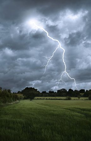 rainstorm: Lightening strikes from a stormy sky over a countryside landscape Stock Photo