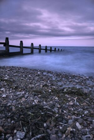 groyne: A timber groyne jets out to the sea under an evening dramatic sunset