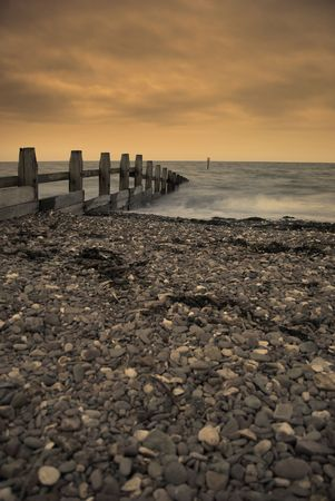 groyne: A timber groyne jets out into the ocean under an orange dramatic sky Stock Photo