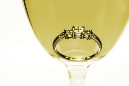 trilogy: Trilogy diamond white gold engagement ring in a glass of white wine. Stock Photo