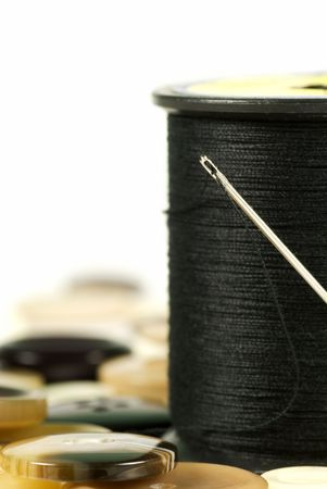 darn: Threaded needle with black cotton surrounded with various buttons Stock Photo