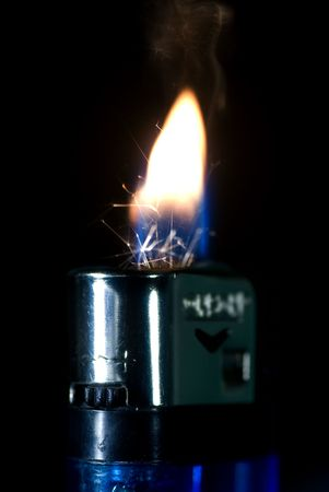 ignited: Blue lighter ignited showing flames and sparks Stock Photo