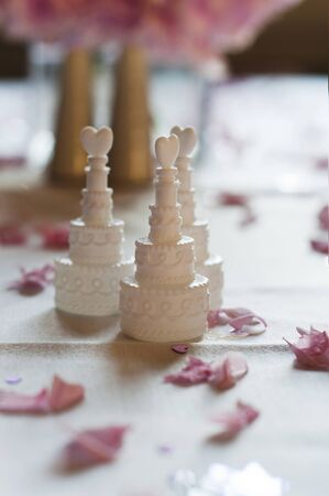 Wedding cake favors arranged on a table with flower petals. photo