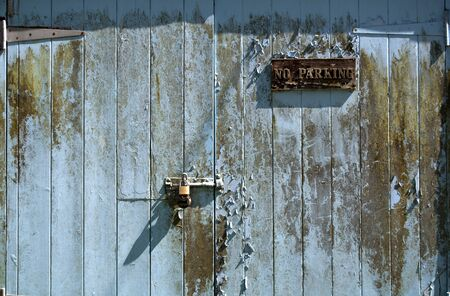 Grungy old rotting garage door with no parking sign