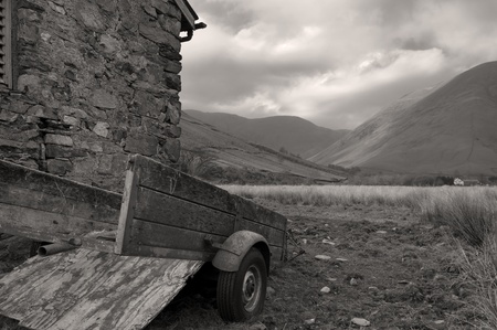 An old trailer sits behind a barn in cumbria England Stock Photo