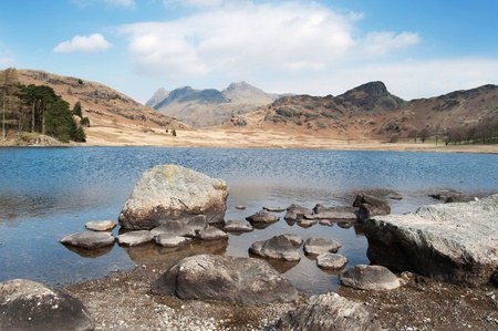 Rocks reaching out into a lake with mountains in the distance Stock Photo - 9019880