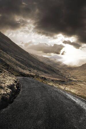 personas en la calle: Bobinado l�der en la carretera a trav�s de un hermoso paisaje accidentado. Foto de archivo