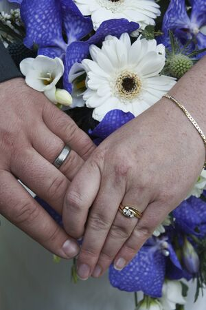 Bride and groom displaying their rings with a beautiful bouquet in the background Stock Photo - 11505576