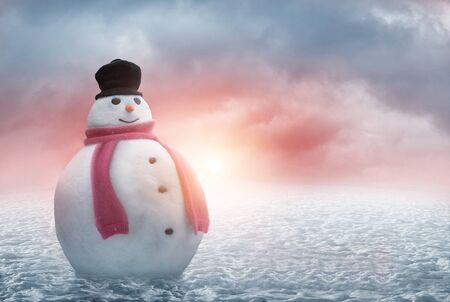 Happy snowman stands in the snow with a beautiful winter sunset