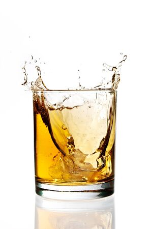 Ice falling and splashing into a glass of whisky