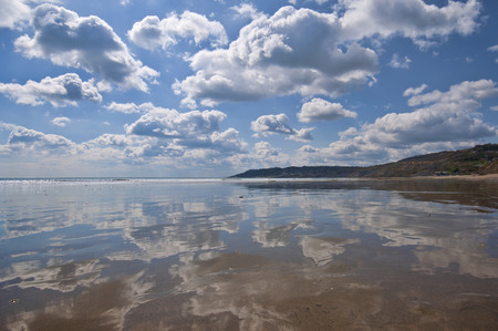 A very strong reflection of the sky across the beach at Charmouth in Dorset, England