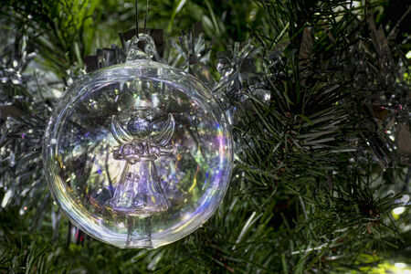 Angle glass Christmas tree bauble hanging from a tree Stock Photo