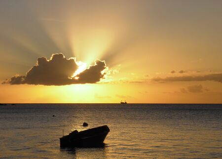 a fishing boat laying in the water while the sun is setting behind a cloud, in the horizon a big trawler is passing by photo
