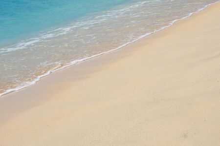 simpson: Turquoise blue calm caribbean sea washes up on sandy beach at Simpson Bay Beach Sint Maarten. Diagonal composition.