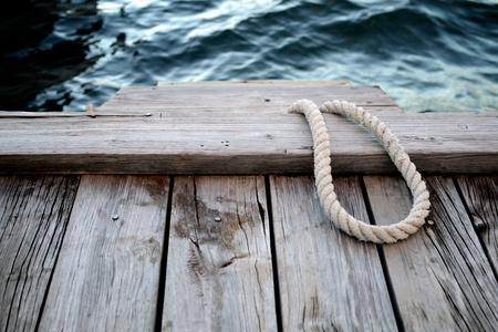 habour: Loop of rope left on wooden pier, awaiting boat to return home to safe habour. Late afternoon shot. Select focus.