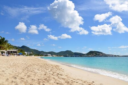 sint: Landscape photo of a white sandy beach on Sint Maarten. Sun is shining, water is calm and the sky is blue with fluffy clouds.