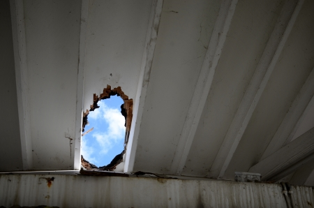 skylight: Puffy clouds on a blue sky seen through a big hole in a house roof  Disastrous heavy rain has damaged the roof and created an undesired skylight
