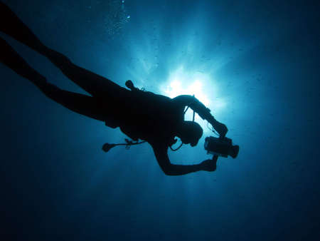Underwater cameraman in back-light. photo