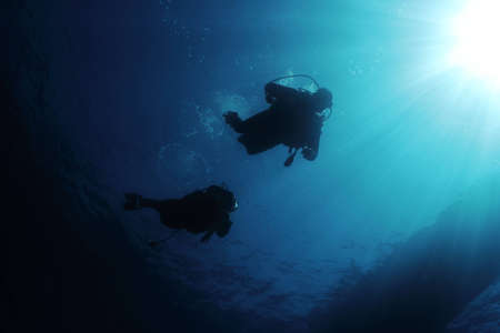 embolism: Divers in back-light and sun rays