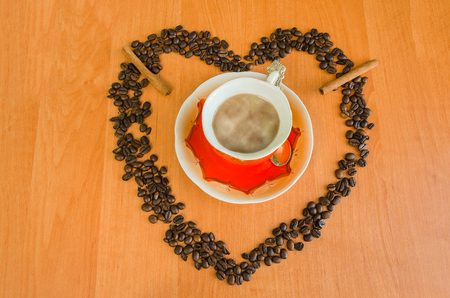 Coffee with milk in a coffee cup and coffee beans on wooden background.
