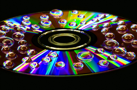 Closeup of water droplets on a multi-colored surface with a beautiful reflection on the surface of a compact disc. Stock Photo - 113639265