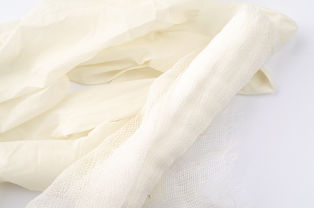 Sterile medical gloves and bandage on a white background.