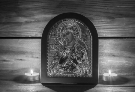 Black and white photo with an Orthodox icon and a burning candle. Stock Photo