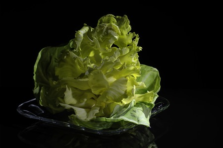 A small bouquet of decorative cabbage in a plate on a black background. Stock Photo