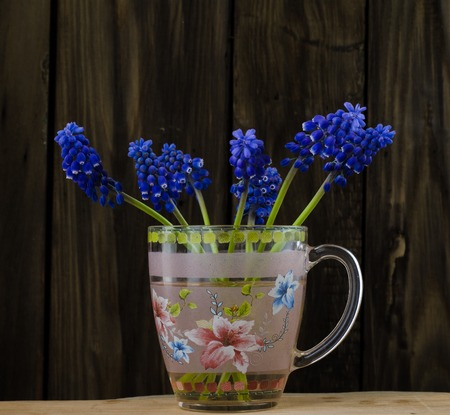 Bouquet of spring flowers in a glass mug on a wooden background.