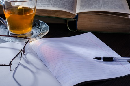 Notebook and books, pen and notebook, glasses and tea are all on the table with the morning light from the window. Stock Photo
