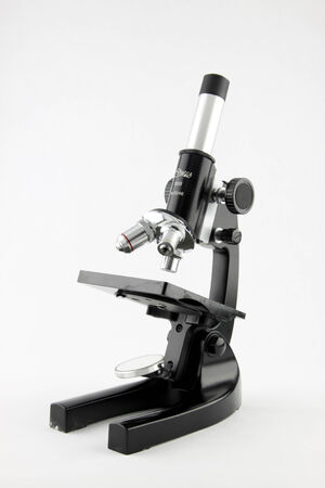 An old classroom microscope isolated on a while background. Stok Fotoğraf