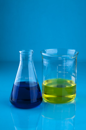 stock photography: Erlenmeyer flask with a blue liquid and a beaker with a yellow liquid