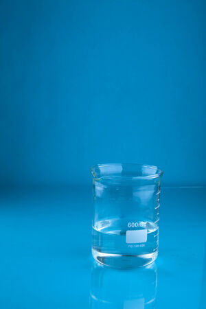 A beaker of water on a blue background