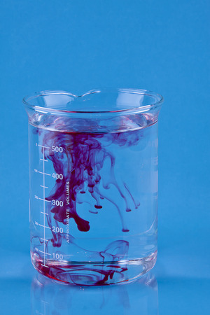 Red food coloring dropped into a Beaker of water.
