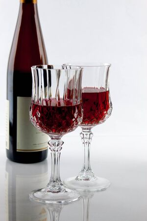 partially: A wine bottle and Two partially filled glasses