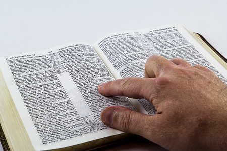Reading a King James bible on a white background