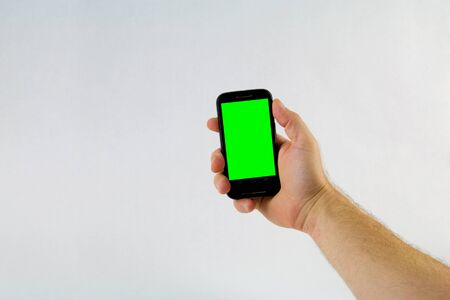 green screen: Male hand holding cell phone on white background with green screen Stock Photo