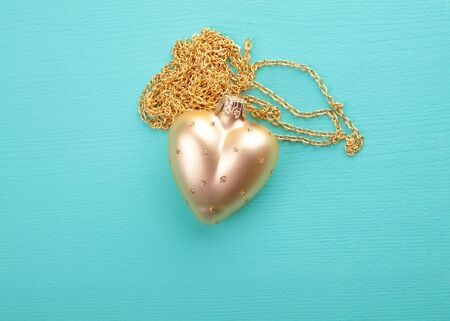 Gold heart with gold chain on the wood texture photo