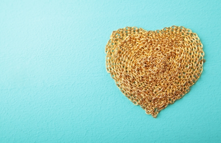 Heart made with gold chain wood texture photo