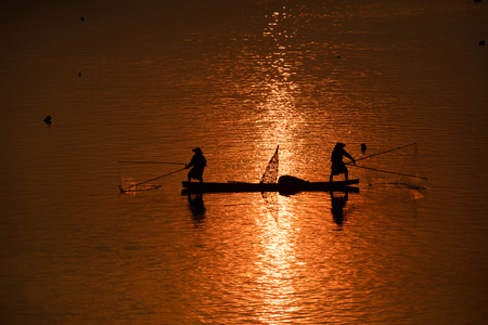 fisherman on boat with sunrise background, the Mekong River in Thailand