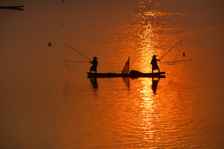 entrapment: Silhouette of  fisherman on boat with sunrise background, the Mekong River in Thailand.