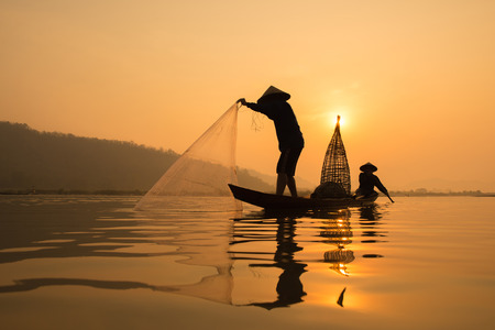 Silhouette of  fisherman on boat with sunrise background, the Mekong River in Thailand.