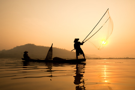Silhouette of  fishermans on boat with sunrise background, the Mekong River in Thailand.